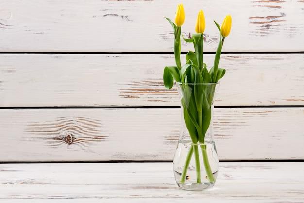 꽃병 유리 꽃병에 있는 노란색 튤립은 방을 선물로 장식합니다.