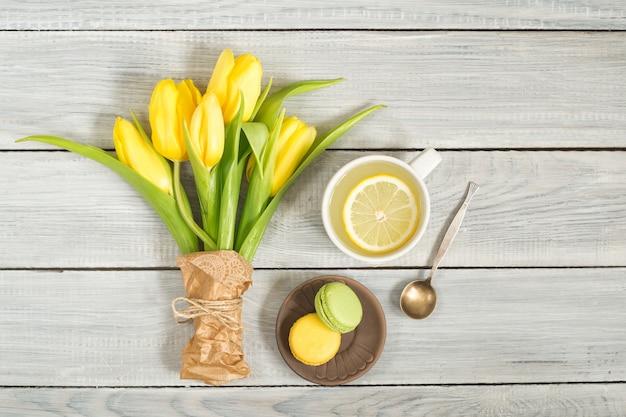 Желтые тюльпаны, чай с лимоном и макароны на белом деревянном столе