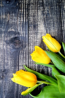 Yellow tulips lie on old vintage wooden table background.