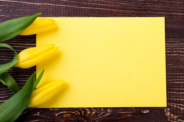 빈 종이 근처 노란색 튤립입니다. 꽃과 종이 조각. 창의성을 위한 공간. 인기있는 인사말 항목.