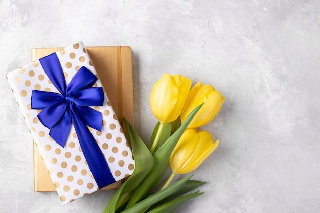 Блокнот и подарочная коробка с желтыми тюльпанами Premium Фотографии
