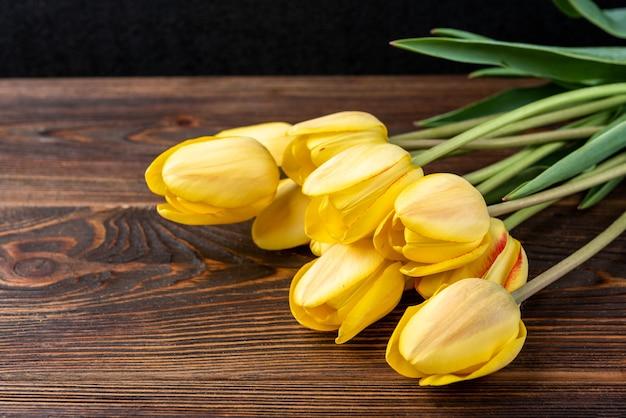 Желтые тюльпаны на темном деревянном столе.