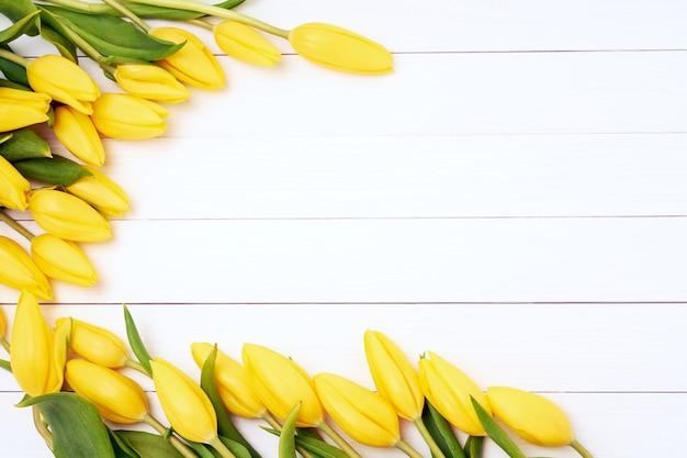 白い木製の背景に黄色のチューリップ。上面図、コピースペース