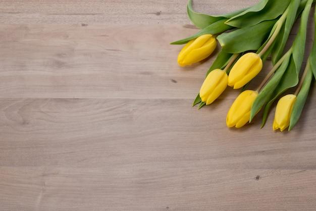 木製の背景に黄色のチューリップ