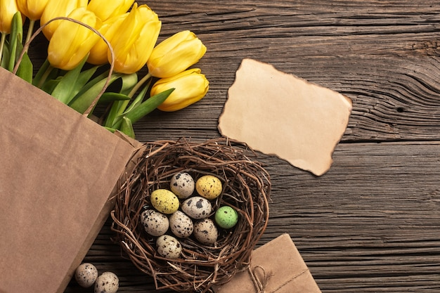Yellow tulips in a paper bag, a nest with easter eggs on a wooden background. top view with copy space.
