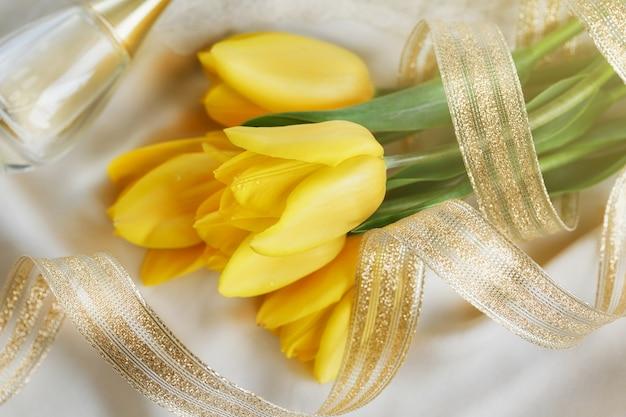 Желтые тюльпаны, духи и золотая лента на шелковом полотне