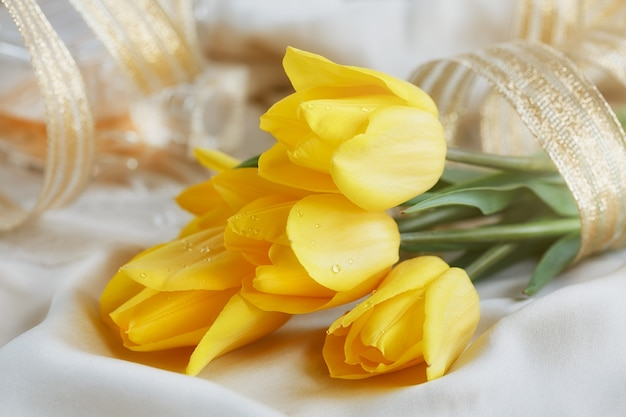 Yellow tulips, perfume and gold ribbon on silk linen