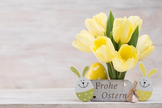 Желтые тюльпаны, весенние цветы и пасхальные украшения.