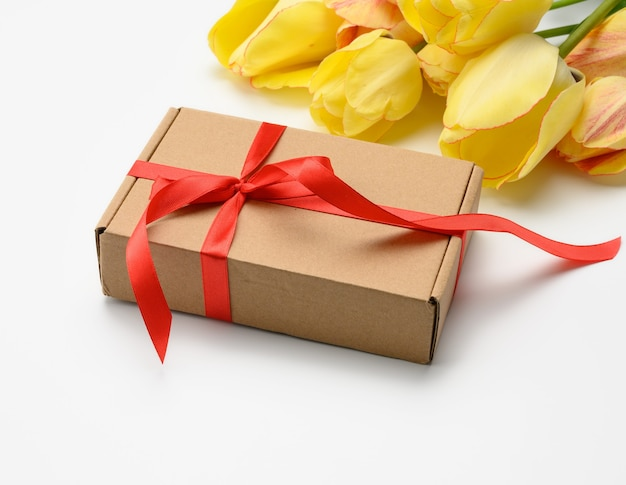 Yellow tulips and square box tied with red ribbon on white surface, festive surface for mother's day, birthday