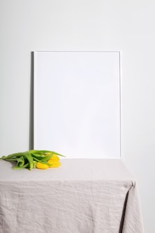 Yellow tulips and white frame on table with beige tablecloth. gray background. copy space