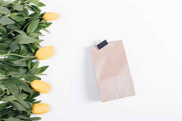 Yellow tulips with green leaves and paper bag with gift on white background, top view