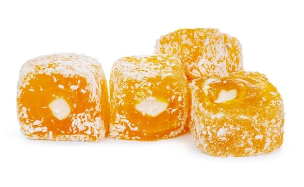 Желтые сладости рахат-лукум, изолированные на белом фоне