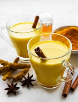 Желтый напиток латте с куркумой. золотое молоко с корицей, куркумой, имбирем и медом на белом фоне мрамора.