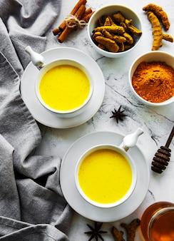 黄色いターメリックラテドリンク。白い大理石の背景にシナモン、ターメリック、生姜、蜂蜜と黄金の牛乳。