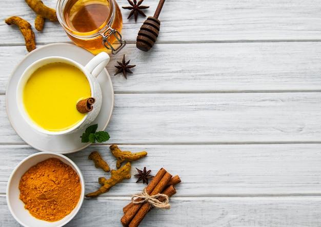 黄色いターメリックラテドリンク。白い木製の背景にシナモン、ターメリック、生姜、蜂蜜と黄金の牛乳。