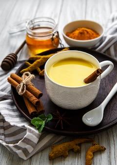 黄色いターメリックラテドリンク。白い木の表面にシナモン、ターメリック、ジンジャー、ハチミツを添えたゴールデンミルク。