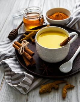 黄色いターメリックラテドリンク。白い木製のテーブルの上にシナモン、ターメリック、生姜、蜂蜜と黄金の牛乳。