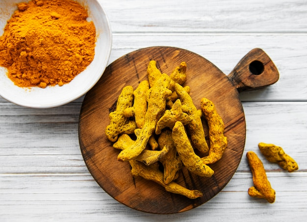 Yellow turmeric powder and dry roots on wooden  surface.