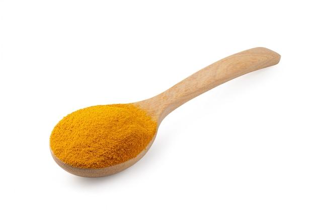 Желтый порошок куркумы в деревянной ложке на белом