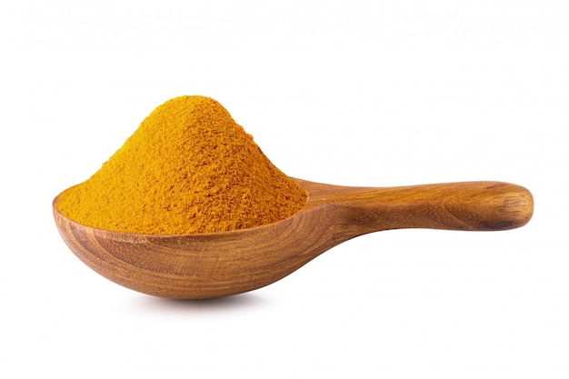 Yellow turmeric powder in a wooden spoon isolated on white