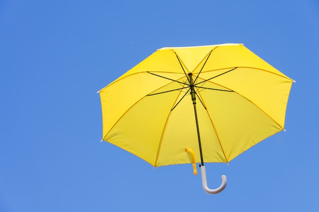 Yellow umbrellas floating in the sky