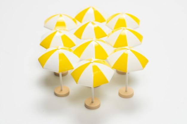 Желтые зонтики на белом фоне. скопируйте пространство.
