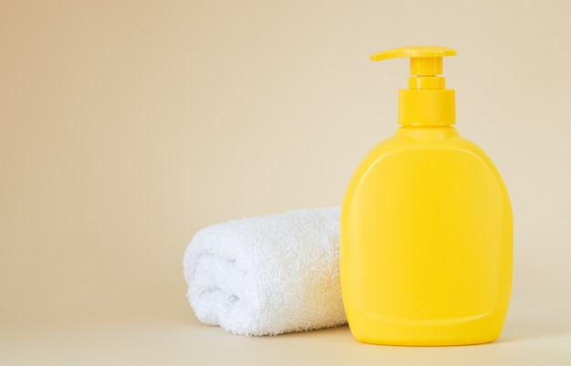 Yellow unbranded dispenser bottle with white towel on beige background, packaging mockup with copy space
