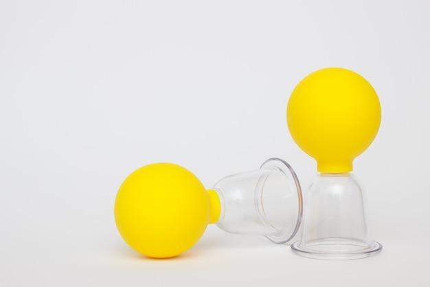 白い背景の上のセルライトに対するマッサージのための黄色の真空瓶