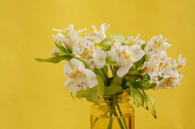 대리석 테이블과 노란색 배경에 흰색 꽃 꽃다발이 있는 노란색 꽃병