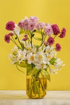 노란색 벽이 있는 테이블에 다양한 종류와 색상의 꽃이 있는 노란색 꽃병