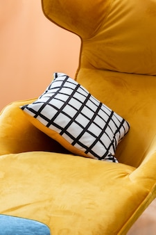 Yellow velvet cosy armchair with double-sided pillow with striped pattern in close-up.