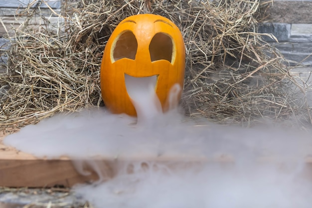 Yellow and very funny happy pumpkin for halloween celebration with lot of smoke or vapor from mouth