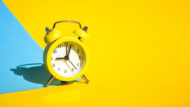 選択的なフォーカス、テキスト用のコピースペースと青と黄色の背景に黄色のヴィンテージ目覚まし時計