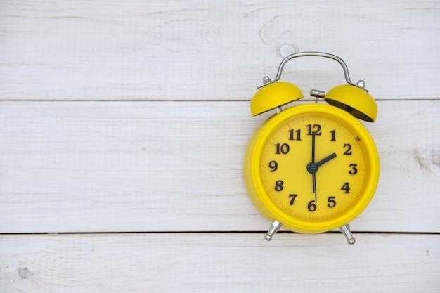 白い木製の背景の上面図に黄色のヴィンテージ目覚まし時計