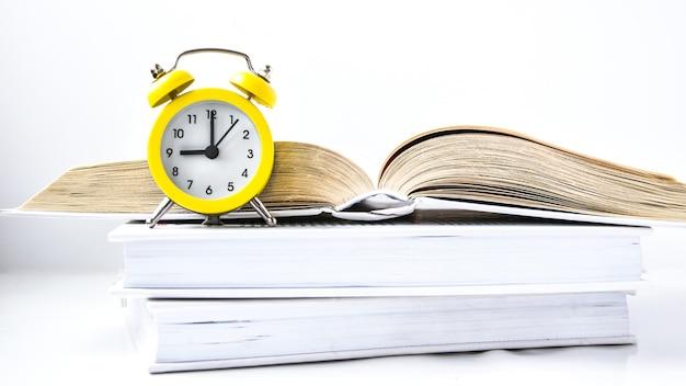 Желтый старинный будильник с книгой на белом фоне, снова в школу, время учиться, знания о богатстве, скопируйте пространство для текста