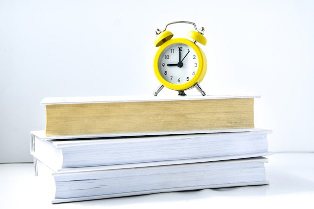 Yellow vintage alarm clock with book on white background, back to school, time to learn, wealth knowledge, copy space for text