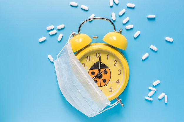 Желтый старинный будильник с белыми таблетками и маской