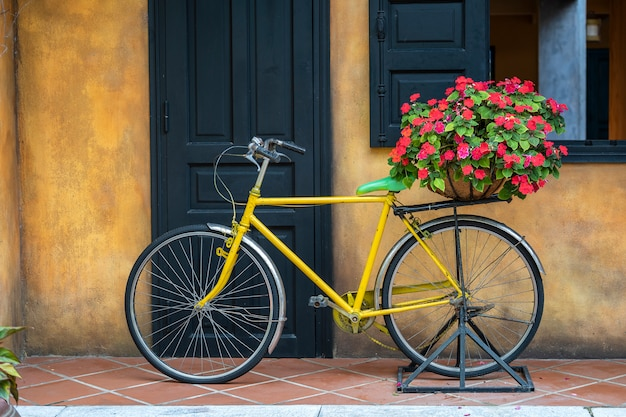 Желтый старинный велосипед с корзиной, полной цветов, рядом со старым зданием в дананге, вьетнам