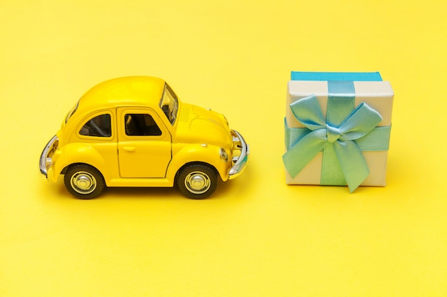 Yellow vintage retro toy car delivering gift box on roof isolated on trendy yellow background