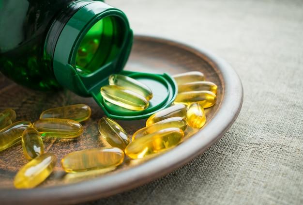 Yellow vitamin d3 (cholecalciferol) gelatine capsules and green bottle