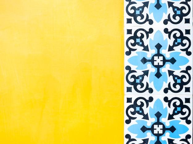 黄色の壁の背景に青いパターン モザイク タイル モロッコ スタイル コピー スペース。ビンテージの伝統的なポルトガルのセラミック タイルの背景。