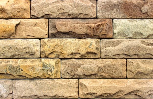 天然石で作られた黄色の壁、装飾的な環境に優しいタイル。背景またはテクスチャ。