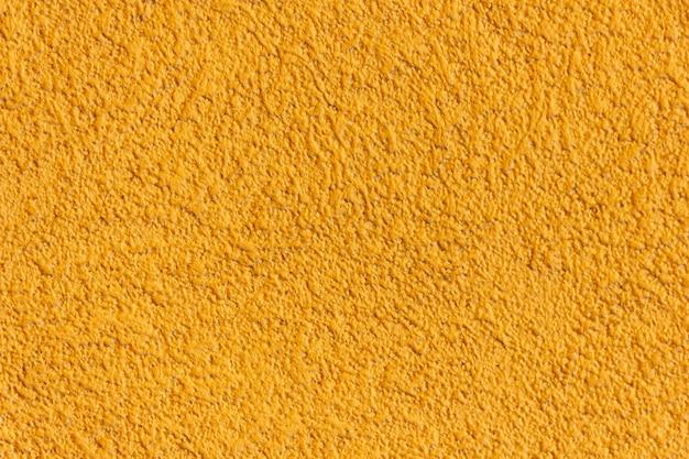 노란색 벽 텍스처입니다. 따뜻한 색 배경입니다. 복사 공간이 있는 벽.