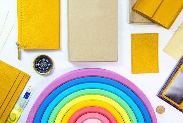 黄色い財布、ユーロ紙幣、コンパス、コイン、子供のおもちゃの虹とアクセサリー