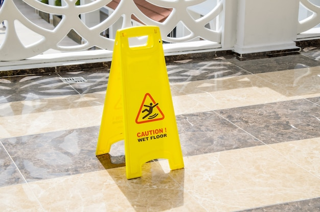 Yellow warning sign caution wet floor on a marble floor in a public area.