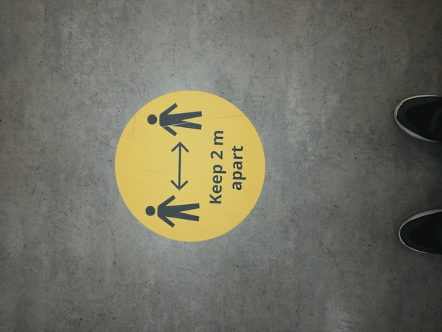 Yellow warning sign to maintain keep distance during covid-19 coronavirus outbreak with figures of men in store and legs of a person in uk