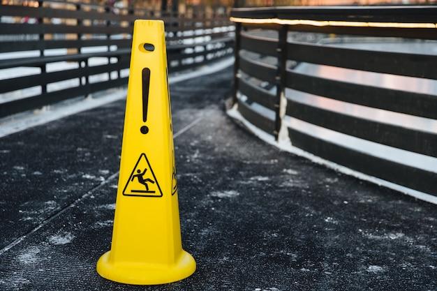 Желтый предупреждающий знак стоит на сером асфальте, покрытом снегом
