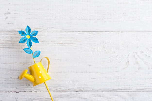 Yellow watering can with flower