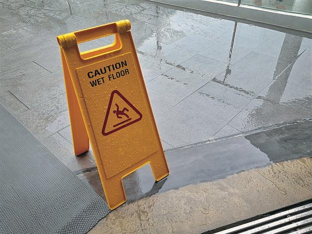 Yellow wet floor warning sign the floor