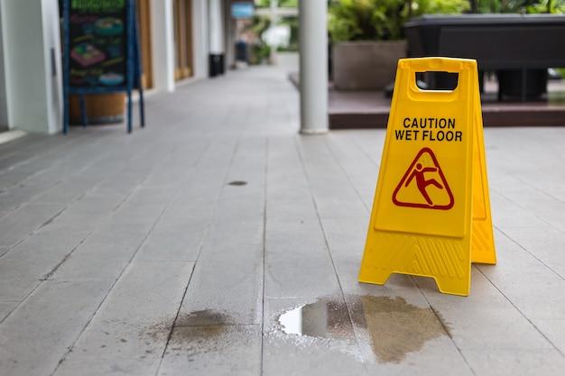 Желтый предупреждающий знак на этаже в коридоре отеля